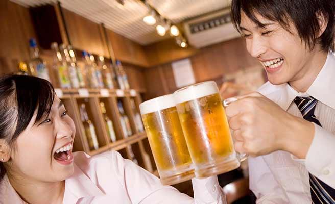 ビールで乾杯する男女の同僚