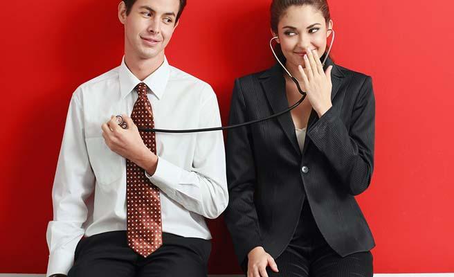 隣に座るネクタイしめた男性の鼓動を聴診器で聞く女性