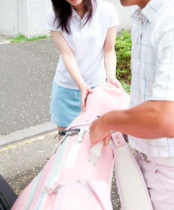 女性のゴルフバッグを車のトランクに積み込む男性