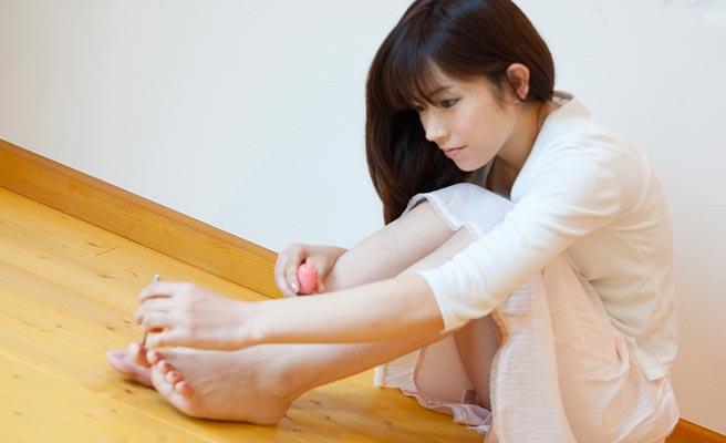 足の指にマニキュアを塗る小柄な女性