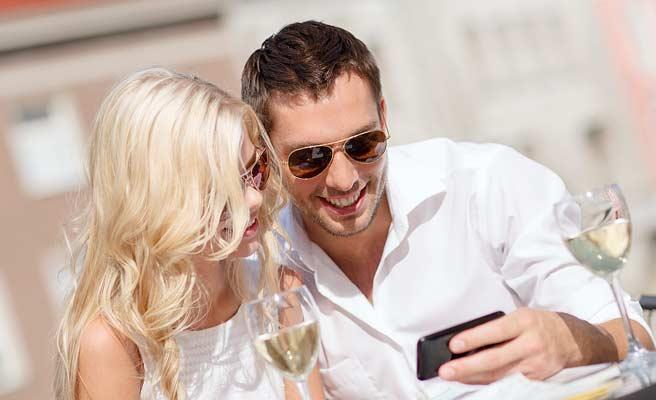 女性とお酒を飲みながらスマホを見る男性