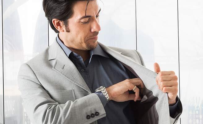 背広の内ポケットから財布を出す男性