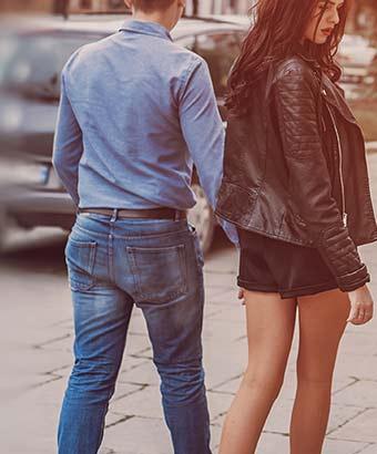 歩道側に女性を歩かせる男性