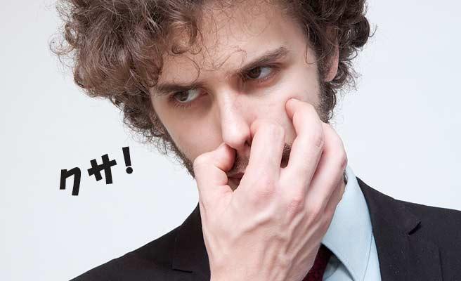 鼻を指でつまむ男性