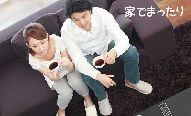 ソファに腰掛けてコーヒーを飲むカップル