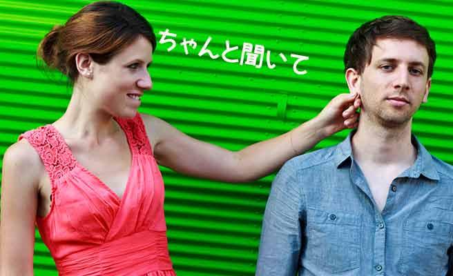 彼氏の耳を引っ張りながら笑う女性