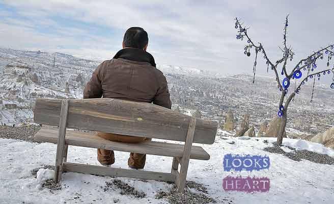 ベンチに座り荒野を見渡す男性