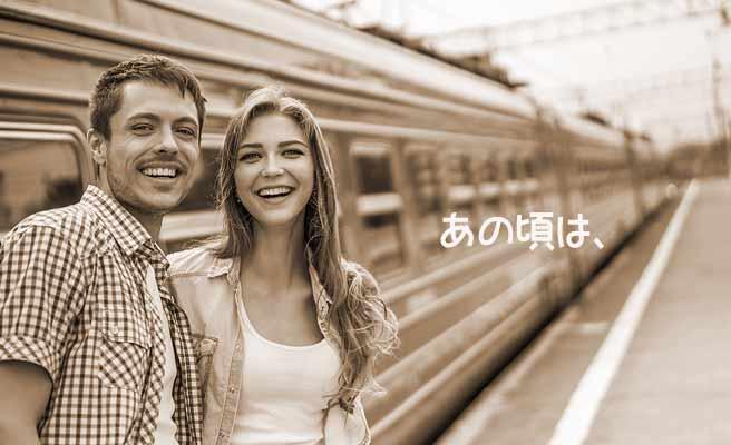 電車から降りて駅のホームに立つカップル