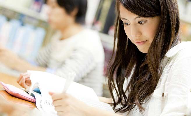 図書館の机でノートに筆記する女性