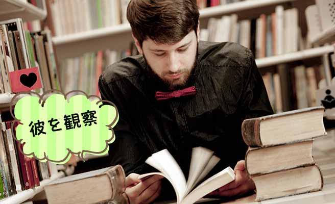 積み重ねた本を読む男性