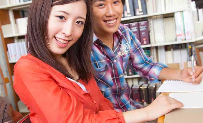 図書館の机で女性と並んでノートに筆記する男性