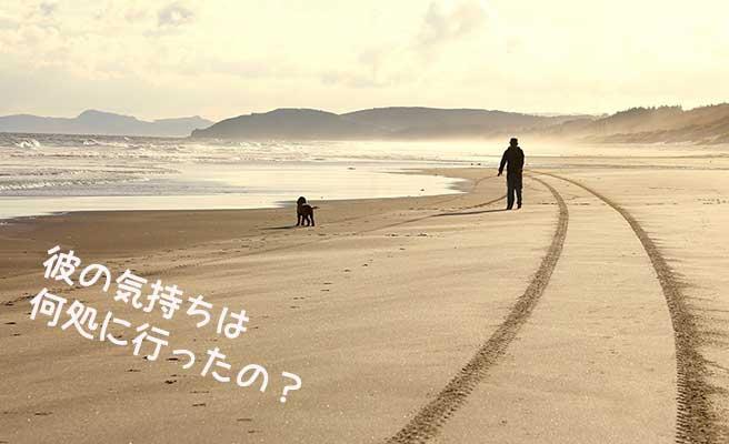 砂浜を犬と散歩する男性