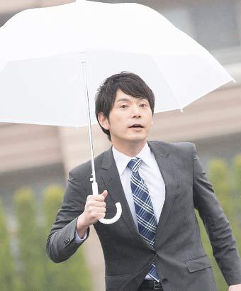 傘をさして歩くスーツ姿の男性