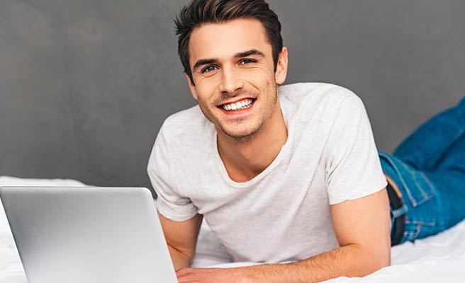 ベッドの上でノートパソコンを開きながら笑顔の男性