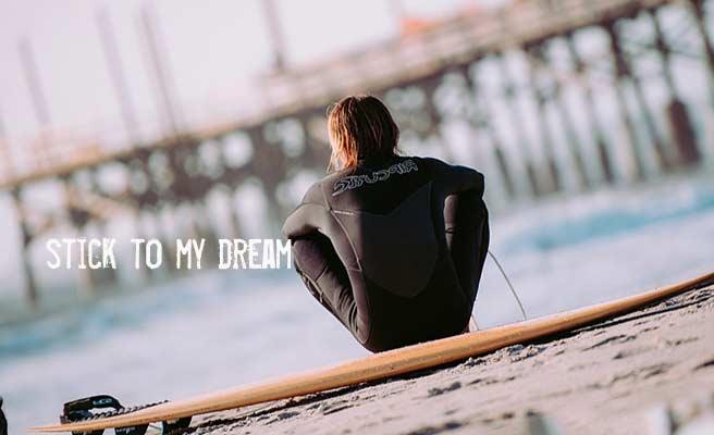 サーフボードに座って波を見てる男性
