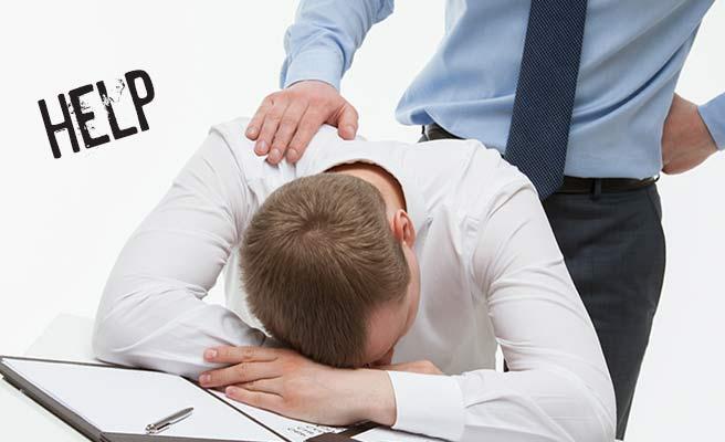 机に突っ伏す同僚男性の肩に手をのせる男性