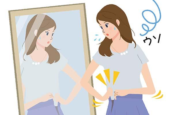 鏡の前でスカートのホックを止めようとしてできない女性