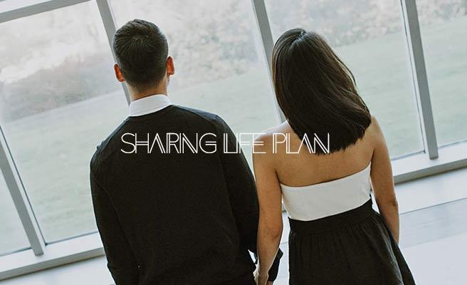 男女が手を繋いで並んで立って窓の外を眺めている