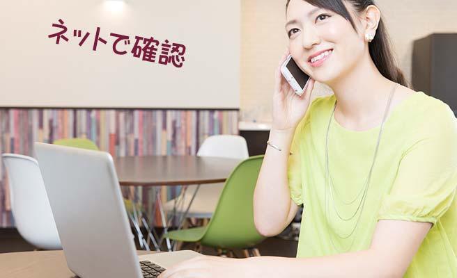 ノートパソコンを見ながらスマホで電話する女性