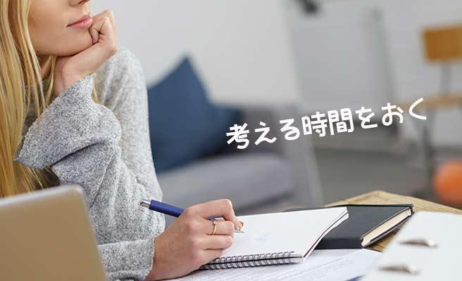 ノートを開いてペンを持ち、考え込む女性