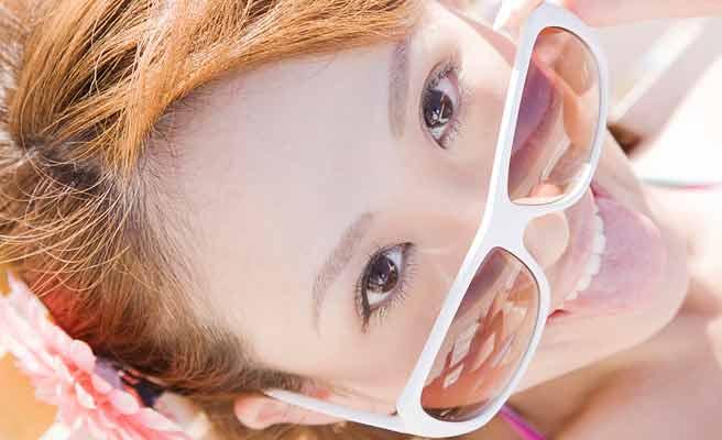 サングラスをかけた女性が日を浴びながら舌を出す