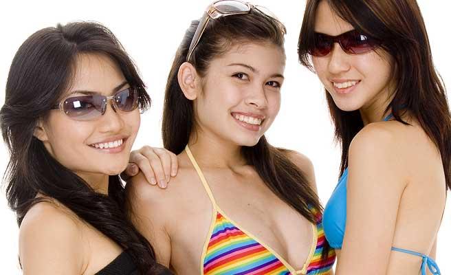 ビーチで水着姿の女性がイエーイ