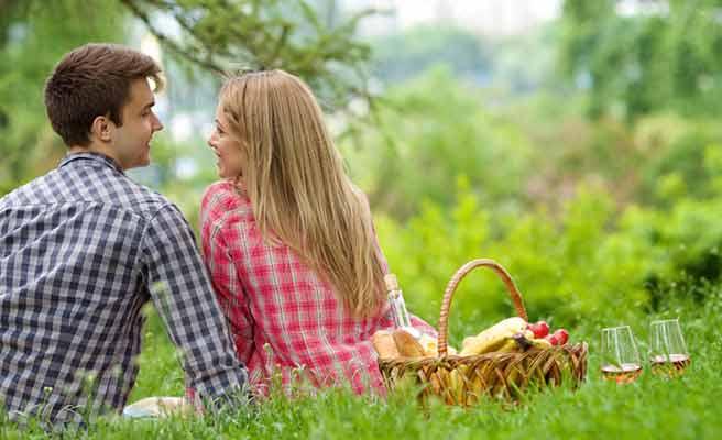 草地に座るカップルと食べ物の入ったカゴ