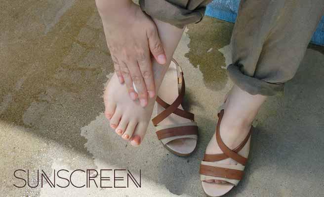 足の甲に日焼け止めを塗ってる女性
