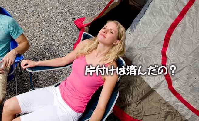 テントの傍で椅子に座って目を閉じる女性