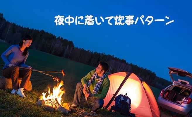 夜のキャンプ場でたき火で食事するカップル