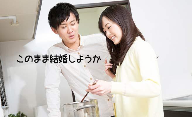 台所で料理する女性と見守る男性