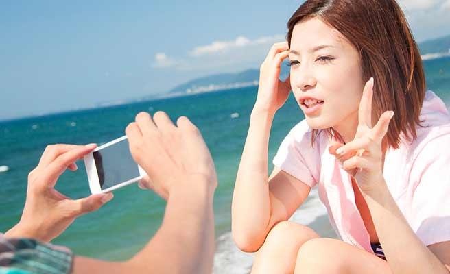 スマホで彼女の写真を撮る男性