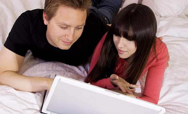二人でパソコンを見るカップル