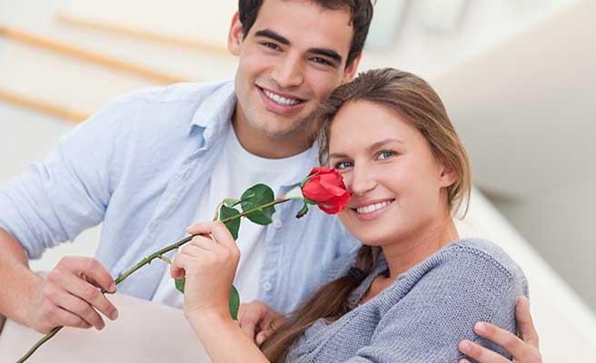 彼氏から貰ったバラ一厘の匂いを嗅ぐ女性