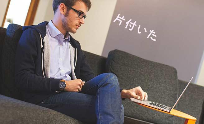 ノートパソコンを見ながら一息つく男性
