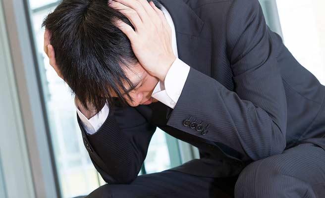 スーツ姿の男性が頭を抱える