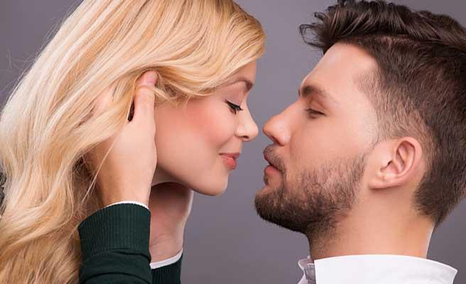 彼女の頭に手を当ててキスしようとする男性
