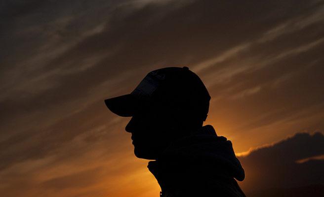 夕刻の空を背景に立つ男性の影