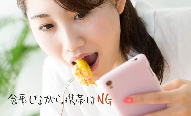 食べながらスマホを見る女性
