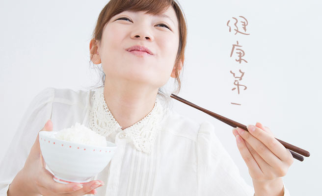 ご飯を食べながら笑顔の女性