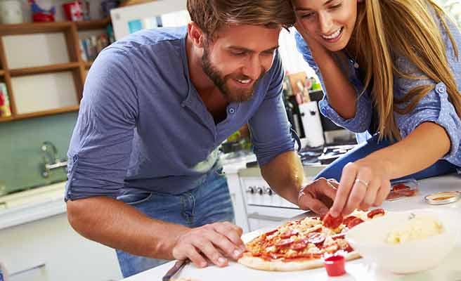 彼女と一緒にピザを調理する男性