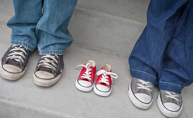 大人の足元に子供の運動靴が置かれている