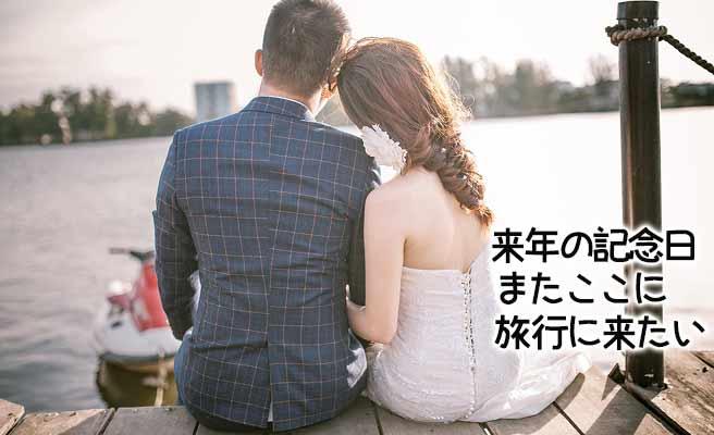 川辺に座って語り合うカップル