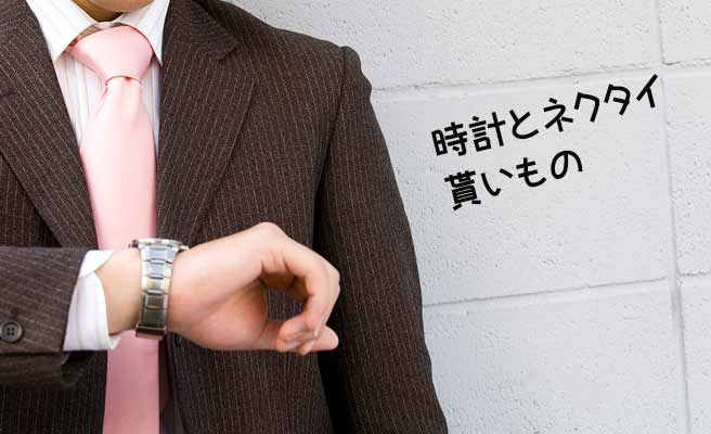 ピンクのネクタイ締めて腕時計を見る男性