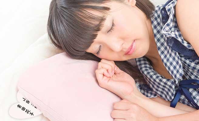 枕の下にハートの紙を入れて眠る女性