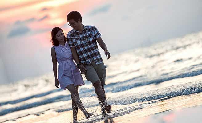 夕暮れの浜辺を歩くカップル