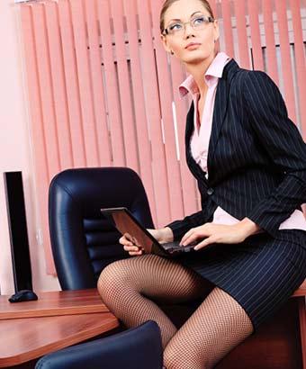 職場の机の上に大胆に座る女性