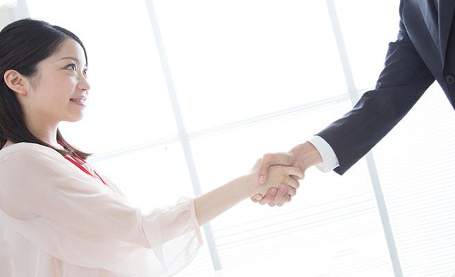職場で男性と握手する女性