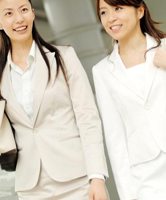 背筋を伸ばして歩くスーツ姿の女性