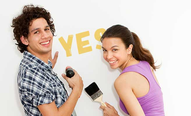 男性の隣で壁にYESと書く女性